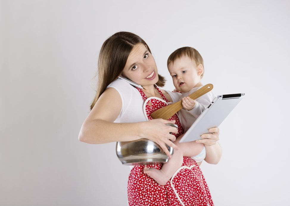 Busy mom holding baby while cooking